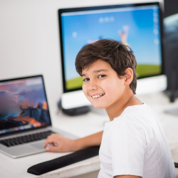 boy smiles while working on the computer