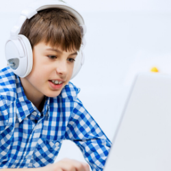 student learning on computer with headphones